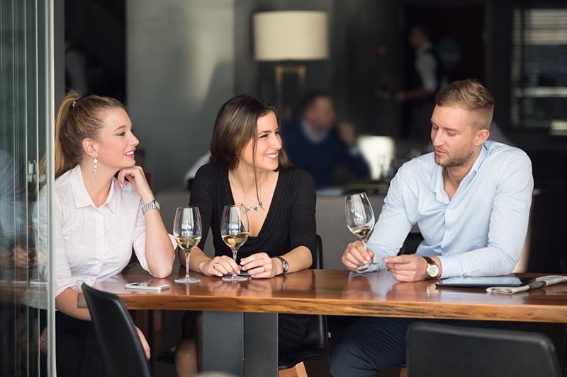 Amigos tomando un vino blanco en un bar