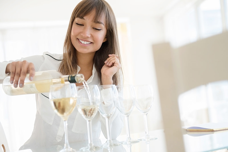 Chica sirviendo copas de vino blanco