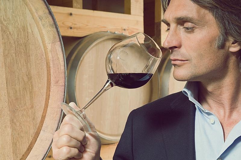 Hombre catando vino entre barricas en la bodega